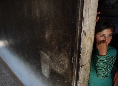 A girl stands near a hole in the wall on the second story of her family home near Idlib, Syria, Thursday, June 14