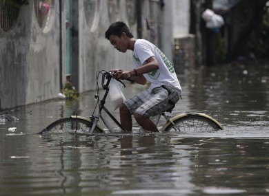 A Filipino pedals his bicycle along a flooded street in suburban Malabon, north of Manila.