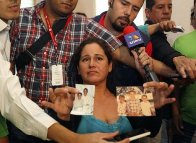 Elodia Leon Vega holds up photos of her sons during a news conference in Guadalajara, Mexico.
