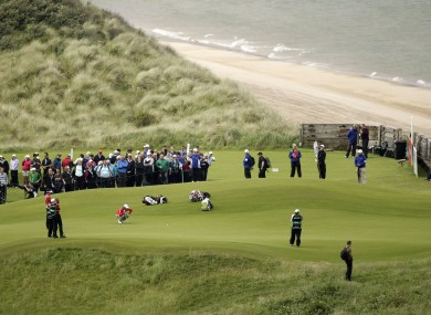 Rory McIlroy, center left, lines up a putt on the 5th green.