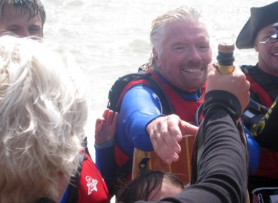Branson gets a bottle of champagne on a beach in Kent today after he abandoned his attempt to cross the English Channel by kite-surf
