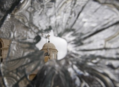 A church dome is seen through a broken window of the Sednaya Convent, which was damaged by artillery fire in Sednaya, north of Damascus, Syria