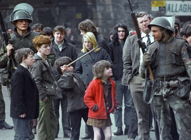 Local children taunt a British soldier as he stands guard in Derry, Northern Ireland on April 13, 1972, after an explosion in the city centre.
