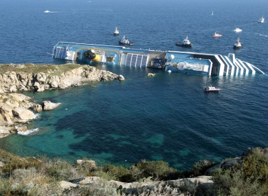 The luxury cruise ship Costa Concordia leans on its side after running aground the tiny Tuscan island of Giglio, Italy, Saturday, Jan. 14, 2012