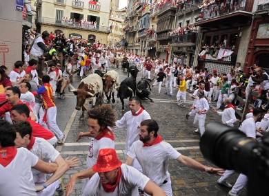 Revelers run on the Estafeta corner with Dolores Aguirre Yabarra ranch bulls during the first running of the bulls at the San Fermin fiestas, in Pamplona northern Spain.