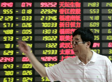 An investor gestures in front of the stock price in Shanghai, China this month