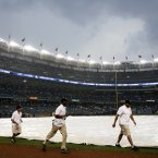 The grounds crew covers the field during a rain delay in the seventh inning of a baseball game between the New York Yankees and Toronto Blue Jays. (AP Photo/Seth Wenig)