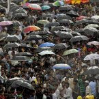 Fans and mourners hold umbrellas as it rains during the funeral of Bollywood superstar Rajesh Khanna in Mumbai, India. (AP Photo/ Rajanish Kakade)