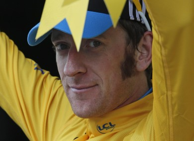 Bradley Wiggins of Britain, wearing the overall leader's yellow jersey, celebrates on the podium of the 17th stage of the Tour de France.