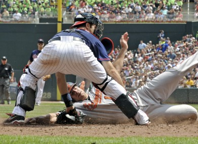 Baltimore Orioles' Chris Davis slides in to score as he beats the tag by Minnesota Twins catcher Joe Mauer in Minneapolis.