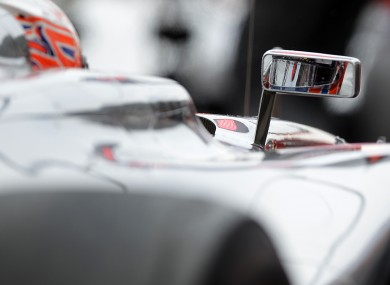 McLaren driver Jenson Button is reflected in the rear mirror of his car during the first training session of the Formula One in Hockenheim, Germany this morning.