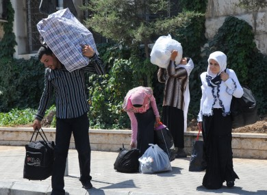 Syrians carry their belongings as they cross into Lebanon at the border crossing point in Masnaa, eastern Lebanon, about 40 kms from Damascus.