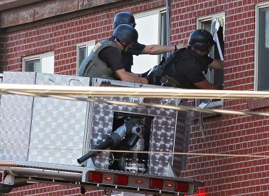 Police use a video camera to look inside an apartment where the suspect in a shooting at a movie theatre lived in Aurora.