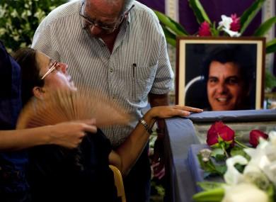 Ofelia Acevedo, the widow of Oswaldo Paya, is commiserated at Paya's funeral in Havana yesterday.
