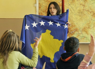 Kosovar Albanian teacher Luljeta Rama introduces Kosovo's new national flag to her class, on the first school day after Kosovo declared its independence in February 2008