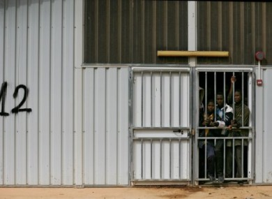 illegal African immigrants and suspected mercenaries stand at a barred door in a prison in Gherian, Libya last February