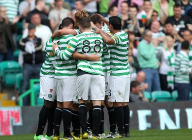Kris Commons is mobbed by teammates after his shot is deflected into the net.
