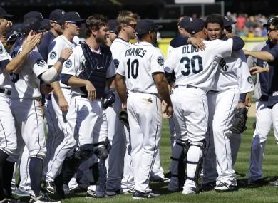 Teammates congratulate Seattle Mariners pitcher Felix Hernandez.