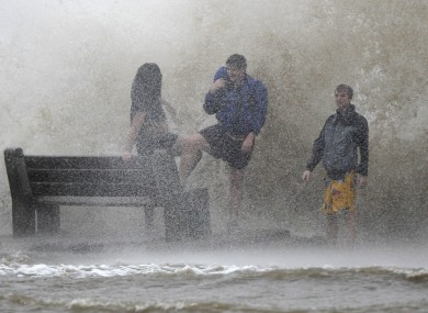 People walk in the storm surge from Hurricane Isaac as the storm approaches landfall in New Orleans.
