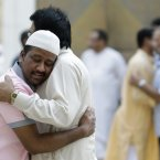 Residents hug each other as they celebrate Eid al-Fitr in Riyadh. (AP Photo/Hassan Ammar/PA)