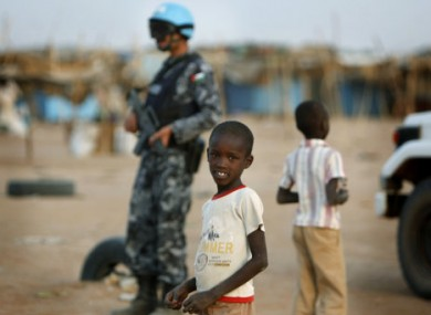 File photo of Sudanese children and a UN peacekeeper bearing a Jordanian flag on his uniform.