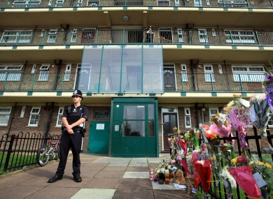 A police officer stands outside a block of flats, in Mitcham, south London, where Natalie Sharp, the mother of Tia Sharp, lives