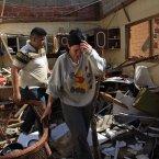 A family walks among debris at their damaged home near Punto Fijo, Venezuela. (AP Photo/Ariana Cubillos/PA)