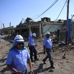 Rescue workers walk past a damaged area on Sunday. (AP Photo/Ariana Cubillos/PA)
