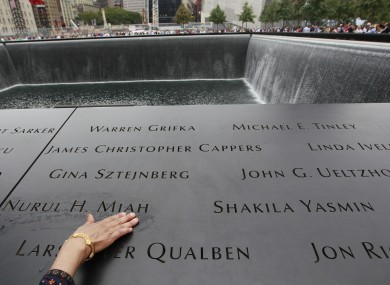 A woman touches her son's name at the National September 11 Memorial in New York City