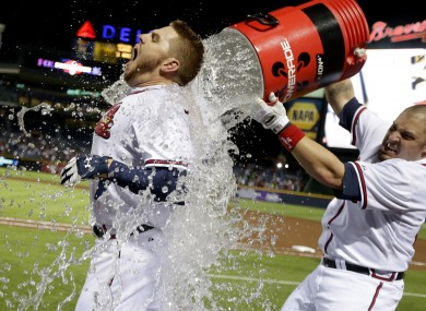 Atlanta Braves' Freddie Freeman, left, is doused with water by Eric Hinske after Freeman hit a home run in the ninth inning as the Braves beat the Marlins 4-3 to clinch at least an NL wild-card playoff berth last night.