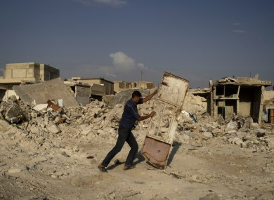 A Syrian man pushes a door away from the rubble of houses destroyed in a government airstrike, in the Syrian town of Azaz on Friday.