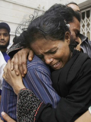 Family members mourn the death of a man outside a mortuary in Karachi, Pakistan, Wednesday, Sept. 12, 2012