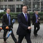 British Prime Minister David Cameron strides into the EU summit in Brussels today. (AP Photo/Yves Logghe)