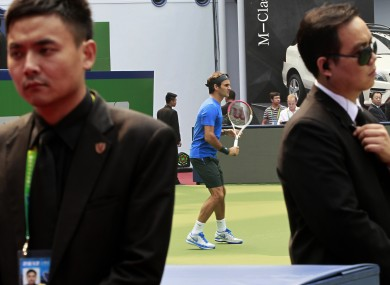 Roger Federer practices as he is guarded by body guards yesterday.