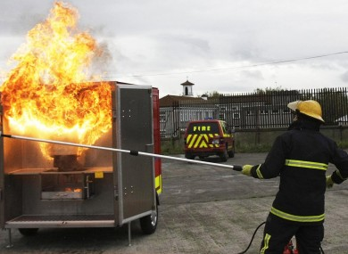 A fire officer demonstrating how not to put out a chip pan fire