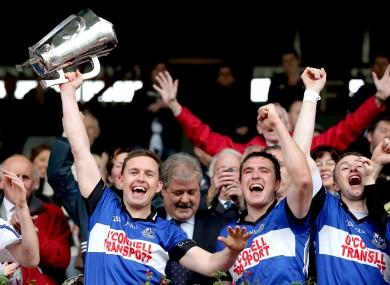 Sarsfields' Joe Barry lifts the trophy alongside Cian McCarthy and Ray Ryan.