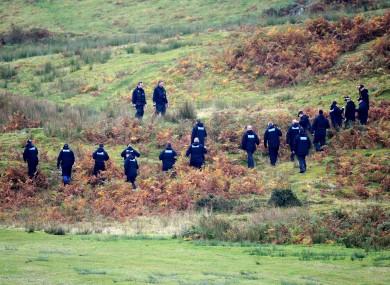 A police team searching land near Machnylleth