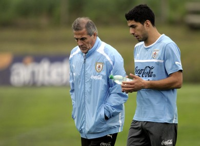 Uruguay coach Oscar Tabarez, left, and striker Luis Suarez walk together on the pitch after a training session on the outskirts of Montevideo yesterday.