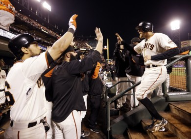 San Francisco Giants' Hunter Pence is congratulated in the dugout after scoring during the seventh inning.