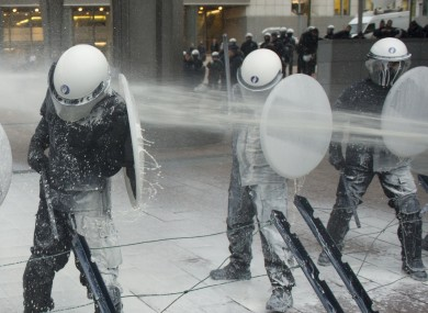 Police officers are sprayed with milk by the European milk farmers during the demonstration in front of the European Parliament building in Brussels yesterday.