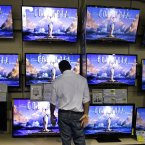 A shopper decides which TV would look best over the fireplace in Franklin, Tennessee, after the store opened at midnight Thursday, beating the traditional Friday opening. (AP Photo/Mark Humphrey)