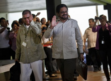 Ivan Marquez, right, and Ricardo Tellez, members of the negotiation team for Colombia's Revolutionary Armed Forces of Colombia, or FARC, wave as they arrive for peace talks in Havana, Cuba