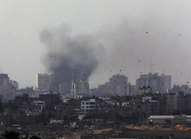 Birds fly as a plume of smoke is seen over central Gaza Strip, after an airstrike by Israeli forces, as seen from the Israel Gaza border on Monday