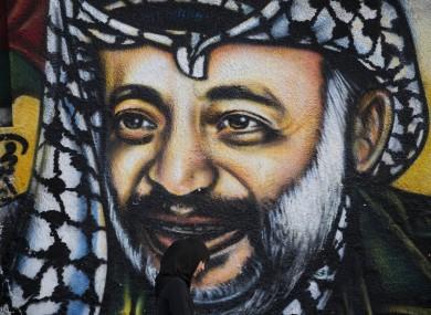 A Palestinian woman walks past a graffiti depicting late Palestinian leader Yasser Arafat in Gaza City.