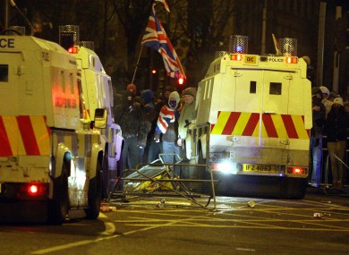 Loyalist protestors carrying Union flags clash with police outside the City Hall in Belfast on Monday.