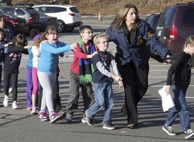 In this photo provided by the Newtown Bee, Connecticut State Police lead children from the Sandy Hook Elementary School
