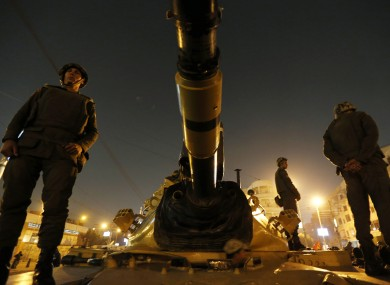 Soldiers stand guard on top a tank in front of the presidential palace in Cairo.