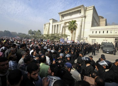 Riot police form a cordon as several thousand supporters of Islamist President Mohammed Morsi surround the Supreme Constitutional Court today.