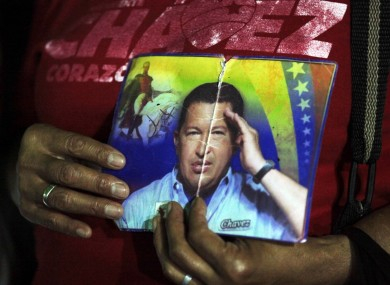 A person holds up images of Venezuela's President Hugo, right, and Venezuela's independence hero Simon Bolivar as people gather to pray for Chavez at Simon Bolivar square in Caracas, Venezuela,