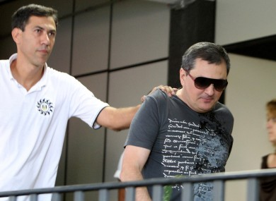 Mauro Hoffmann, right, co-owner of the Kiss nightclub, is escorted by police as he voluntarily surrenders at a police station in Santa Maria, Brazil.